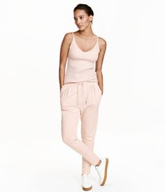 Powder pink. Jersey joggers with wide elastication and a drawstring at waist. Decorative gathers at top, side pockets, and tapered legs.