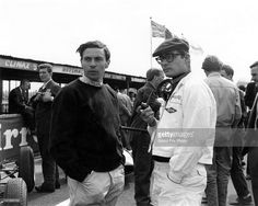Jim Clark of Great Britain and driver of the #5 Team Lotus Lotus 24 Climax V8 talking with Masten Gregory, driver of the #9 UDT Laystall Racing Team Lotus 18/21 Climax S4 before the start of the XVII B.A.R.C 200 race on 28th April 1962 at the Aintree Circuit, Liverpool, United Kingdom.