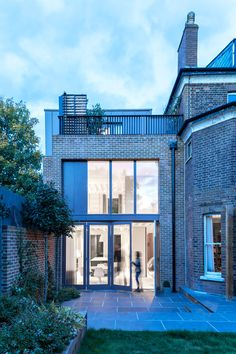 Alexander Martin Architects has added a three-storey extension to a Victorian house in north London, featuring brick walls and a big window facing out to the garden