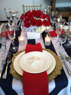 Red, white, blue, and gold nautical tablescape theme.  Blue and white stripped tablecloth, gold charger plate, gold rimmed glasses, red napkins, and starfish decor. White ceramic flower vase with red roses and white and blue hydrangeas. Willowdale Estate, a weddings and events venue in Topsfield, Massachusetts. WillowdaleEstate.com