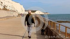 senior-man-walking-his-cocker-spaniel-walkway-under-telscombe-cliffs-sussex-southern-england