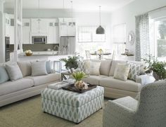 A lovely, clean style living room in an open concept main floor living area consisting of the living room, kitchen, and a small dining area. The living room has beautiful layered patterns in coordinating colors of blue and accents of yellow. The ottoman serves a double purpose as a coffee table.
