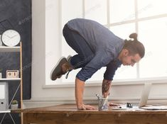 Flexible man practicing yoga at workplace photo by Milkosx on Envato Elements