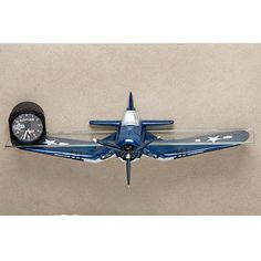"""F4U Corsair Shelf Here's the ideal accessory for the home bar or office of any aviation enthusiast! The F4U Corsair Shelf is sculptured of resin and painted in precise detail. The front silhouette of a Corsair with a spinning propeller is depicted in 3-D; a tempered glass shelf measuring 22.5""""l x 3""""w completes the presentation."""