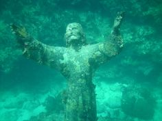 """Christ of the Abyss, San Fruttuoso, Liguria, Italy. """"Il Cristo degli Abissi"""" is a submerged bronze statue of Jesus. It was placed in the water on 22 August 1954 at approximately 17 metres depth, and stands c. 2.5 metres tall."""