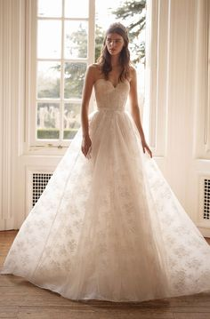 This semi-sheer French lace and silk tulle ball gown is highlighted by an expertly draped corset bodice, sweetheart neckline, and dreamy, gossamer silhouette. Keep the veil simple—an unembellished tulle veil will do the trick.
