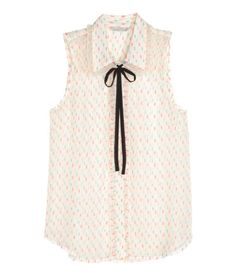 Check this out! Sleeveless blouse in airy chiffon with ruffle trim around collar and button placket. Detachable decoration at neckline. Concealed buttons. - Visit hm.com to see more.