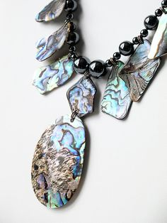 Fine Jewelry - I made this high fashion necklace with fine-stones, Abalone shell pieces and knotted it with silk thread. It's made with 3, 5, 6, 8, 10-mm hematite beads, 6x12-mm oval hematite beads, approximatively 18x30-mm Abalone shell pieces and one 33x51-mm central oval Abalone shell piece. Its 8x18-mm hook and eyes clasp and 5-mm jump rings are in sterling silver (.925).
