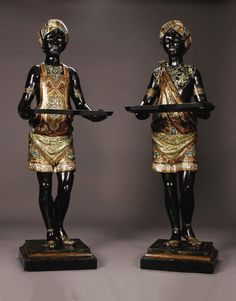 Large Pair Nineteenth Century Venetian Blackamoors  Expertly carved and brilliantly painted male and female standing figures with polychrome enamel and gilt turbans, slippers and robes, holding forth removable trays, standing on custom made lacquered plinths.
