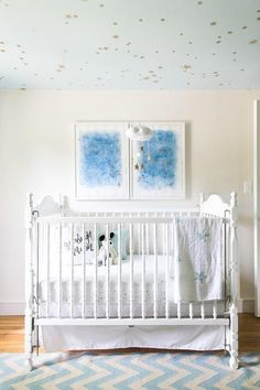 Chic nursery decorated with blue abstract art, white vintage crib dressed in Aden & Anais Night Sky Starburst Classic Crib Sheets. Ceiling painted in Behr Rainwashed matches the Baby Jives Star Cloud Mobile in Gold that hangs above the crib | Designed by