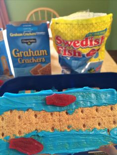 Super Easy moses red sea snack! graham crackers + blue icing + swedish fish. You can make some with water parted and some all blue with fish to show before God parted it!