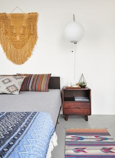 Bohemian bedroom. Mixed ethnic flatweaves and a fringed wallhanging... plus a cute midcentury nightstand!