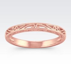 This romantic wedding band is crafted in quality 14 karat rose gold.  The milgrain detailing gives the design a vintage feel.
