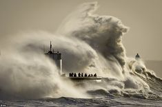 Astonishing: People photograph enormous waves as they break on Porthcawl, South Wales, where very strong winds and high seas create dangerous conditions.. January 2014