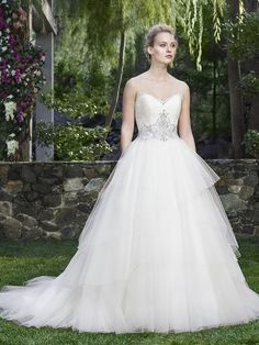 Calla Lily's sweetheart neckline is rimmed in dainty lace detailing, and the silky satin bodice is expertly beaded in a tantalizing design. Supple layers of tulle fall in sweet, asymmetrical layers on Calla Lily's skirt and cascade into a cathedral length train.