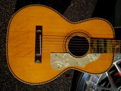"""Stromberg Voisinet Parlor Guitar 1920. The coolest Parlor guitar from this period not often seen these days, grainey natural finished top w/colorful herringbone rosette & body trim, very grainey & colorful Brazilian Rosewood back & sides, Mahogany neck w/side loaded headstock for tuners, white mutha-o-toilet pickgard & green forest painted fingerboard, pyramid bridge, finally it is autographed by the infamous """"Whispering Bill Anderson"""", member of the Grand Old Opey in March 1987."""