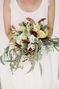 "Beautiful ""Australian"" Bridal Bouquet Which Includes: Blue Eryngium Thistle, White Orchids, White/Mint Flannel Flowers, White Wax Flower, Star Of Bethlehem, Yellow Roses, Cranberry Ranunculus, White Queen Anne's Lace, Eucalyptus + Green, Rust & Chocolate Colored Foliage>>>>"