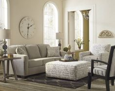 OTTOMAN COFFEE TABLE  Light toned living room stands over grey hardwood flooring, with neutral grey sofa next to text-patterned white armchair and matching square cushion ottoman.