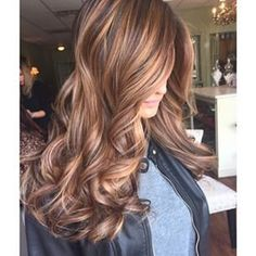 Dark brown hair with caramel highlights.