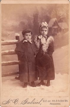 Two very well dressed children pose in their winter coats and hats at the studio of H. C. Gabriel in Philadelphia, Pennsylvania.