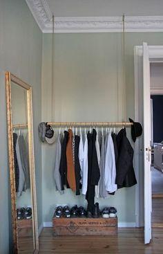 Une tringle, un miroir doré et un coffre pour créer un dressing ouvert