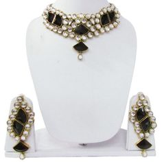 Gold tone with black & white acrylic and faux gemstones.