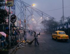 A man sweeps the road gathering rubbish to burn on a small street side fire on chilly misty morning in Kolkata, West Bengal, India. For image Singing Exercises, Image Please, West Bengal, Any Images, Kolkata, Portrait Art, Dawn, Asia, Street View
