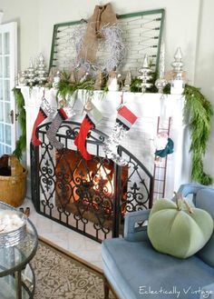 LOVE this fireplace @ Eclectically Vintage. The old box spring, garland, and mercury glass trees LOVE IT!