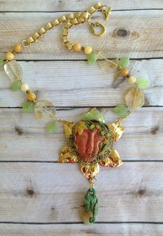 "July Boheiman Vibe Challenge .. Her name is ""Geneva"" Boheiman Necklace .. Made with polymer clay and she is attached to a B'sue Bezel and then that is mounted onto a large flower .. hanging from bottom is a Citrine Stone that I made into a flower bud .. Chain & leaves are also from B'sue, Stones are Citrine and beads are Yellow Jasper .. Designed by Jann Tague .. CLEVER DESIGNS .. https://www.facebook.com/JewelsByJann"