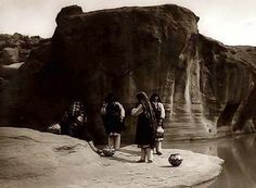 """Morning Chat"".  Four Acoma women with pottery vessels gathered at watering hole. The women are having a nice conversation"