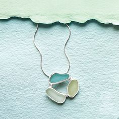 """This elegant necklace is built around a trio of translucent, sea glass """"pebbles""""--discarded glass that is shattered, shaped, and smoothed by the ocean before washing up on the beaches of Hawaii."""