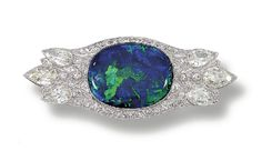 OPAL AND DIAMOND BROOCH    Set at the centre with an oval cabochon black opal, within a pierced surround millegrain-set with single- and circular-cut diamonds, enhanced at the terminals with six principal pear-shaped diamonds,  fitted case. Art Deco or Art Deco style.