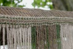 Header band stitched to top beam of ww loom -card woven warp at beginning of a project on the warp weighted loom