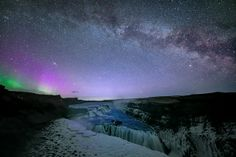 Milky Way and aurora borealis over a waterfall in Iceland