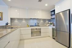 White poly kitchen with CesarStone Shitake benchtops and a combination of glass and tile backsplash