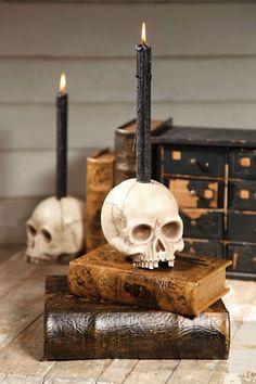 Realistic skull candle holder with black taper candle