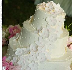 Sweet and stylishly simple best describes the couple's three-tiered chocolate-chip-flavored cake with white buttercream icing. *Light pink fondant flowers with a silver bead center cascaded down one side.*