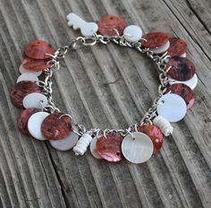 Coin MOP Shell Up-Cycled Chain Bracelet $14.00  This sweet bracelet is made with white and coral colored mother of pearl shell coins and white puka shells on up-cycled antique silver twisted chain with a mother of pearl key charm and a lobster clasp.