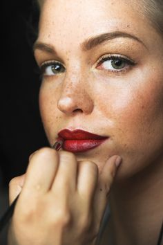 Perfect fall/winter makeup: Black mascara, taupe shadow, structured brow, and rich red lips. Classic.