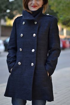 The Quart coat is a short, double breasted, fitted coat with a high stand-up collar, inseam pockets, long sleeves with zipped cuffs.