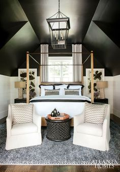 smart design of an attic bedroom. wainscoting halfway up the wall, then the remainder is painted black and downplays all the crazy angles.