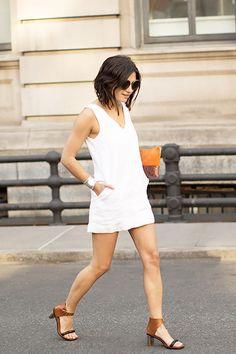 Garance Doré of Garance Doré in a white mini dress + heels + orange clitch