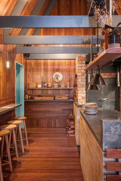 """Um beco estreito entre duas casas, em Adelaide, Austrália, recebe um aconchegante bar e restaurante. Projetado pelo estúdio Sans-Arc, o Pink Moon Saloon é resultado de """"uma narrativa ao ar livre, uma memória de infância, de alimentos cozidos na fogueira e acampar na floresta. O bar e restaurante é dividido em duas pequenas cabanas. Entre as duas cabanas, um pátio, com vista para os prédios um pouco mais altos que estão ao redor."""