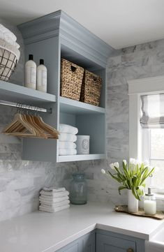 Jillian Harris's laundry home. Love the soft blue cabinets, marble tile backsplash, space for hanging clothes. Cute accents on the open shelving and counter top.