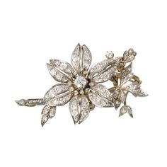 "An antique diamond and silver-topped corsage brooch <br /> <span style=""font-variant: small-caps;"">circa 1870</span> <br /> centering an old mine-cut diamond, weighing approximately 0.80 carat and accented throughout with old mine and single-cut diamonds; estimated total remaining diamond weight:  2.10 carats, brooch is further set with numerous rose-cut diamonds, with articulated flower and suspended section. <br />  <br /> 19.7 dwt.; Length: 4 in. <br /> <span style=""font-variant…"