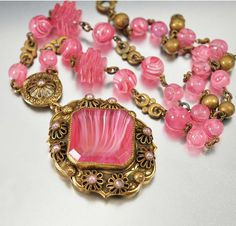 An ornate pendant having gold brass flowers with pink pearl centers and a chain…