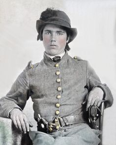 Young Confederate Cavalry soldier wearing a plumed slouch hat imported english snake belt with one holstered revover and another pistol in his belt.