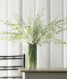 White Dendrobium Orchids: Understated Beauty - One of the most spectacular and prolific members of the orchid family, the dendrobium symbolizes love, joy, and friendship. Here, several are paired with bear grass for a stunning all-white presentation.