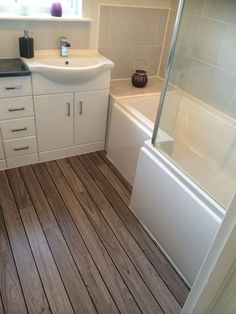 This white bathroom furniture looks great alongside the wooden laminate flooring