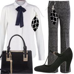 Il fiocco nero chiude l'abbottonatura della camicia bianca, indossata su un paio di pantaloni con gamba larga; le scarpe hanno cinturino davanti e tacco alto, la borsa di taglio geometrico è nera con inserti color argento. Per completare un paio di orecchini a pendente in argento e onice.